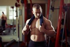 Bodybuilder d'homme fort avec la serviette sur son cou dans la détente de gymnase Image stock