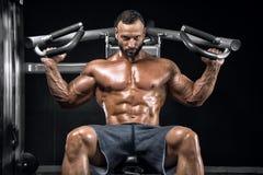Bodybuilder dans un gymnase de pose photos stock