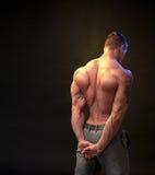 Bodybuilder on a dark background Royalty Free Stock Photo