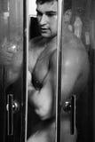 Bodybuilder in de douche stock afbeeldingen