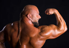 Bodybuilder  demonstrating muscles of the back and arms Royalty Free Stock Images