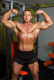 Bodybuilder demonstrating pose in fitness club Royalty Free Stock Image