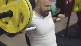 Bodybuilder, der Übung auf Simulator in der Turnhalle tut Mann, der Kastenmuskeln biegt stock footage