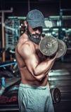 Bodybuilder, der Übungen mit Dummköpfen tut Stockbilder
