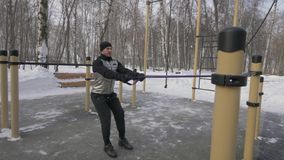 Bodybuilder, der anaerobe Übung mit Expander auf Wintertraining im Freien ausbildet stockfotos