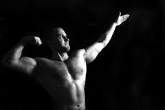 Bodybuilder, der in der Gymnastik aufwirft lizenzfreies stockfoto