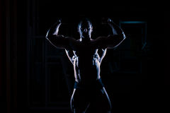 Bodybuilder, der in der Turnhalle steht und Muskeln biegt Stockbilder