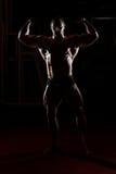 Bodybuilder, der in der Turnhalle steht und Muskeln biegt Lizenzfreie Stockbilder