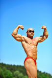 Bodybuilder, der draußen seine Muskeln biegt Stockfoto