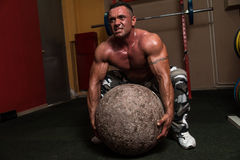 Bodybuilder, der eine Übung des starken Mannes versucht Lizenzfreie Stockfotografie