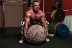 Bodybuilder, der eine Übung des starken Mannes versucht Stockbild