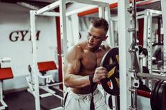 Bodybuilder, der für Übung mit Barbell in der Turnhalle sich vorbereitet stockfotos