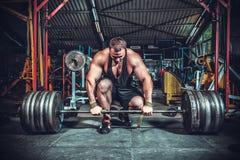 Bodybuilder, der für deadlift von Barbell sich vorbereitet Stockfotografie
