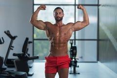 Bodybuilder, der Front Double Biceps Pose In-Turnhalle biegt stockfoto