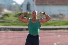 Bodybuilder, der Front Double Biceps At Tennis-Platz durchführt stockbild