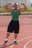 Bodybuilder, der Front Double Biceps At Tennis-Platz durchführt lizenzfreie stockfotos