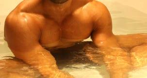 Bodybuilder, der im Badezimmer badet stock footage