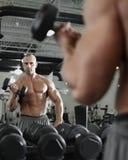 Bodybuilder, der mit bumbbells Gewichten an der Turnhalle ausarbeitet Stockfotos