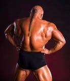 Bodybuilder, der Muskeln der Rückseite und der Arme demonstriert Stockfoto