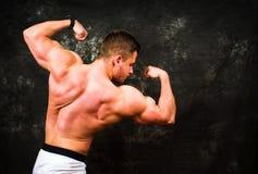 Bodybuilder, der Muskeln gegen dunklen Hintergrund biegt Stockfotografie