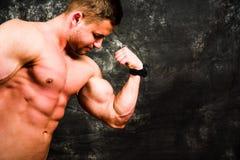 Bodybuilder, der Muskeln gegen dunklen Hintergrund biegt Stockbild