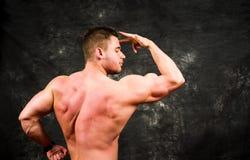 Bodybuilder, der Muskeln gegen dunklen Hintergrund biegt Lizenzfreie Stockfotografie