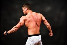 Bodybuilder, der Muskeln gegen dunklen Hintergrund biegt Stockbilder
