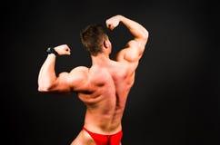 Bodybuilder, der Muskeln gegen dunklen Hintergrund biegt Lizenzfreies Stockfoto