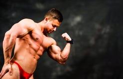 Bodybuilder, der Muskeln gegen dunklen Hintergrund biegt Lizenzfreie Stockfotos