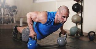 Bodybuilder, der Stoß upsat die Turnhalle während ausarbeitet und tut Lizenzfreie Stockfotos
