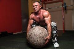Bodybuilder, der versucht, einen Stein aufzuheben Stockbilder