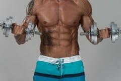 Bodybuilder die Bicepsen met Domoren op Grey Background uitoefenen stock afbeelding