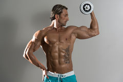 Bodybuilder die Bicepsen met Domoren op Grey Background uitoefenen Royalty-vrije Stock Afbeeldingen