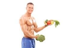 Bodybuilder die een broccolidomoor en een plaat houden Royalty-vrije Stock Foto