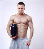 Bodybuilder die een zwarte plastic kruik met weiproteïne op witte achtergrond houden Royalty-vrije Stock Afbeeldingen