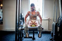 Bodybuilder die en bij de gymnastiek, de benen en de voeten uitwerken opleiden Stock Foto