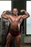 Bodybuilder die Front Double Biceps Pose uitvoeren Royalty-vrije Stock Afbeelding