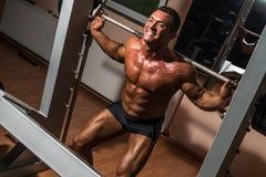 Bodybuilder die hurkzit met barbell in gymnastiek doen royalty-vrije stock foto's