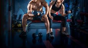 Bodybuilder die met domoorgewichten bij de gymnastiek uitwerken Het jonge paar werkt bij gymnastiek uit Aantrekkelijke vrouw en k royalty-vrije stock afbeeldingen