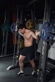 Bodybuilder die met een barbell hurken Bodybuilder die met barbell werken Geschiktheidsmens die hurkzit met barbell doen bij de g Stock Foto's
