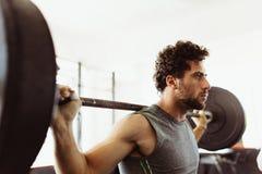 Bodybuilder die met zware gewichten uitwerken stock foto