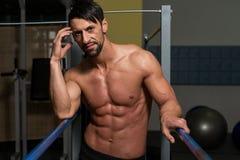 Bodybuilder die na het Uitoefenen op Brug rusten Stock Foto's