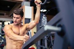 Bodybuilder die oefening op geschiktheidsmachine doen in gymnastiek Stock Fotografie