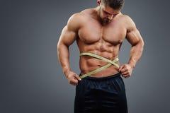 Bodybuilder die taille met meetlint meten stock foto