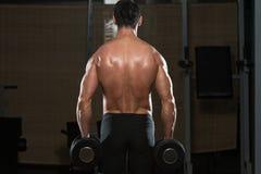 Bodybuilder die Trapezius met Domoren uitoefenen Stock Afbeeldingen