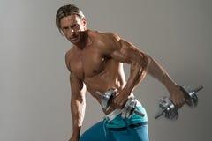 Bodybuilder die Triceps met Domoren op Grey Background uitoefenen Stock Afbeeldingen