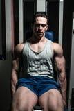 Bodybuilder die zwaargewicht oefening voor benen op de uitbreidingen van het machinebeen doen stock afbeeldingen