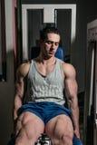 Bodybuilder die zwaargewicht oefening voor benen op de uitbreidingen van het machinebeen doen royalty-vrije stock foto
