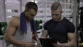 Bodybuilder is discussing the results of his training with male instructor in the modern gym. Couch is holding notepad and explaining what to do to the athlete stock video
