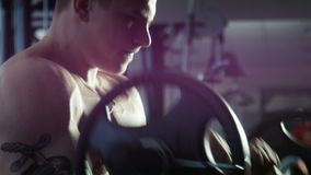 The bodybuilder does exercise with a bar. The weightlifter does exercise in a gym stock video